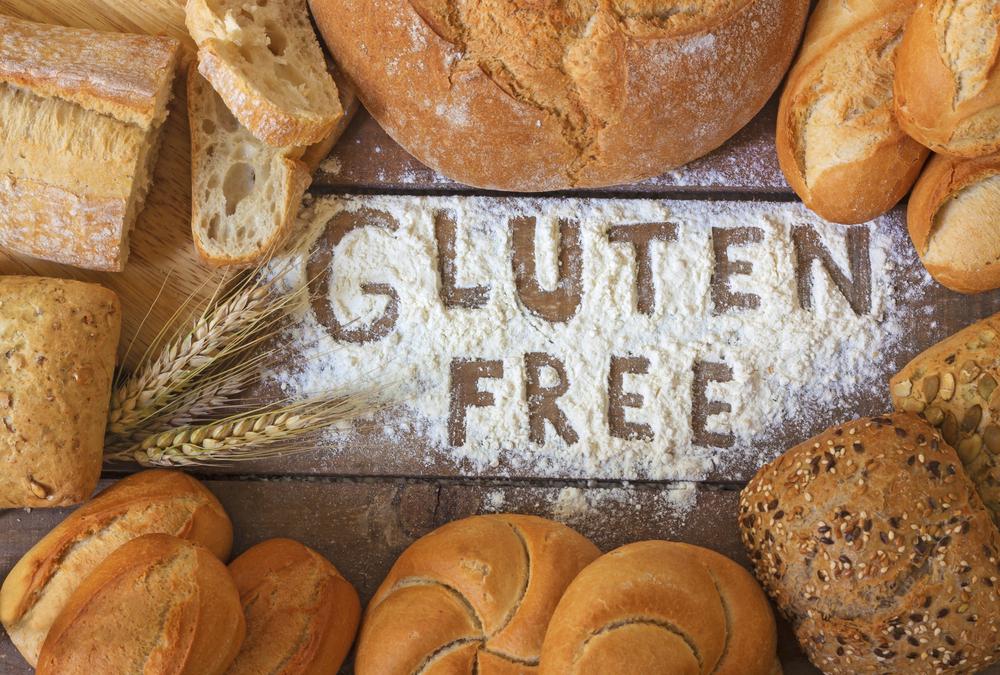 """Breads surround the words """"Gluten Free"""" written in flour"""