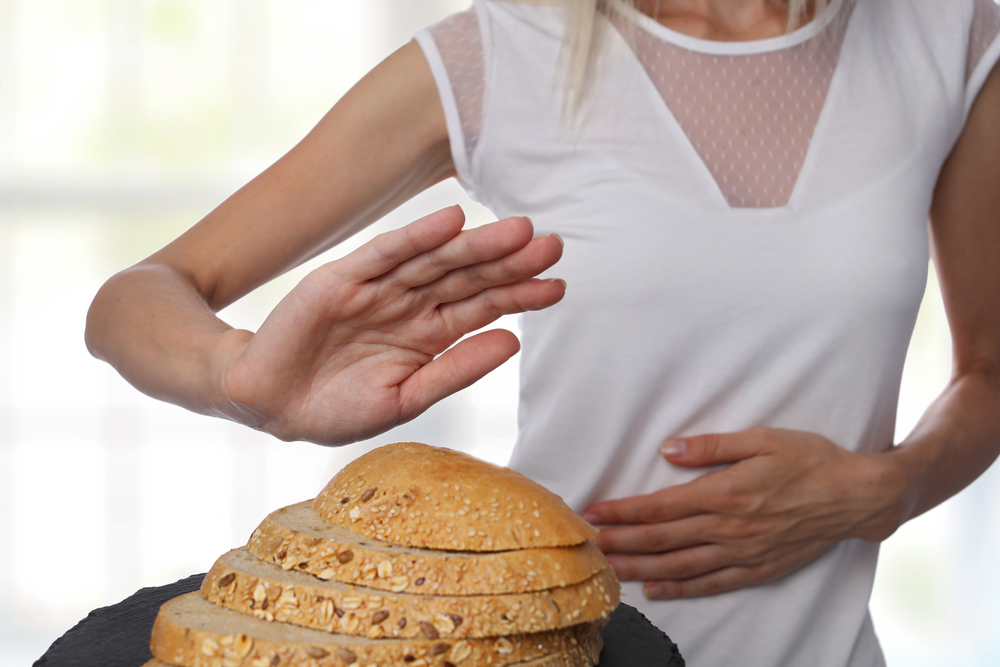 A woman with cramping pushes away bread--gluten sensitivity