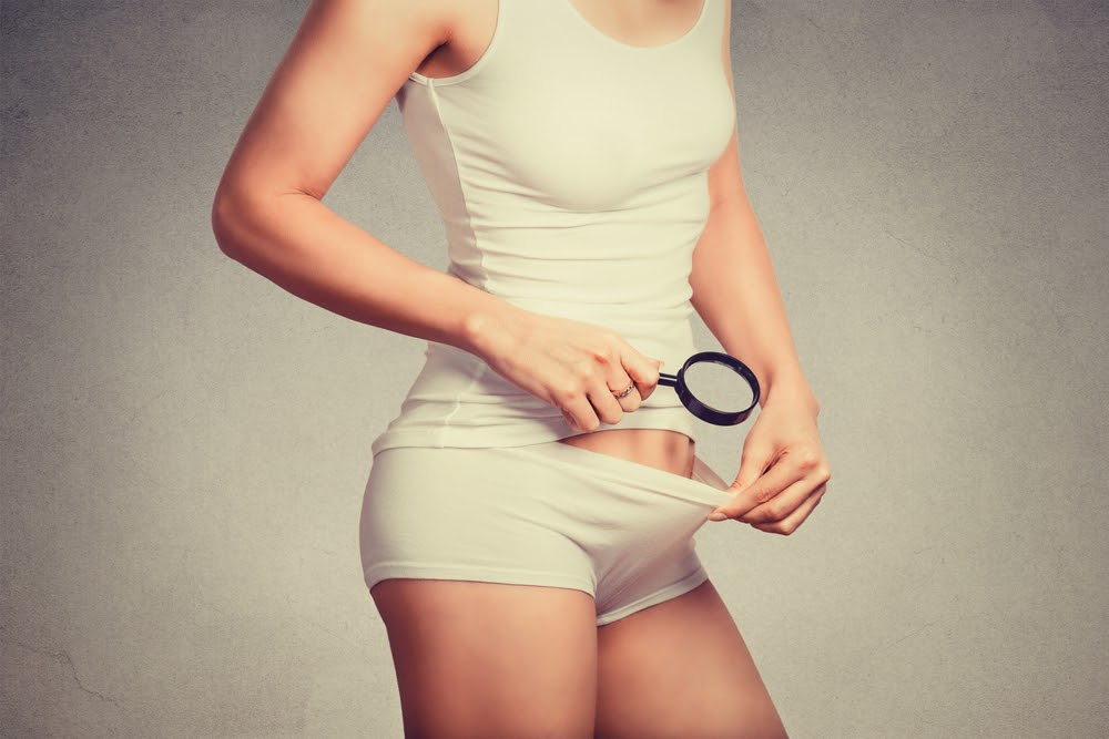 A woman uses a magnifying glass to look for signs of STDs near her pelvis